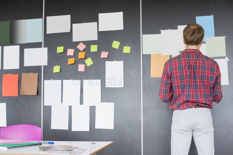 Vue arrière d'homme d'affaires analysant des documents sur le mur au bureau créatif images libres de droits