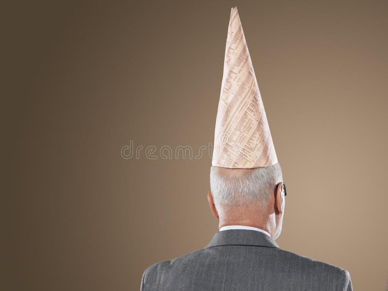 Vue arrière d'homme d'affaires Wearing Dunce Hat photographie stock libre de droits