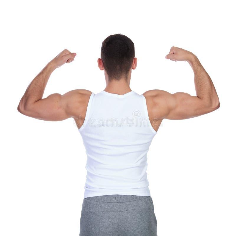 Vue arrière d'homme fort dans le tricot fléchissant son biceps photos stock