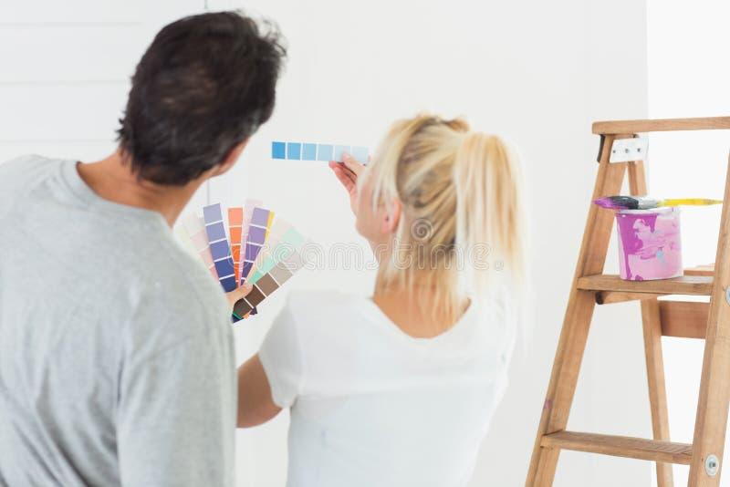Vue arrière d'un couple choisissant la couleur pour peindre une salle image libre de droits
