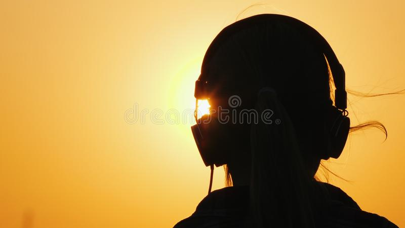 Vue arrière d'un enfant avec des écouteurs écoutant la musique et admirant le coucher du soleil et un grand ciel orange image stock