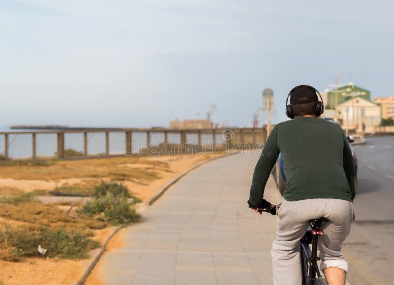 Vue arri?re d'un homme avec des ?couteurs montant la bicyclette par la mer images libres de droits