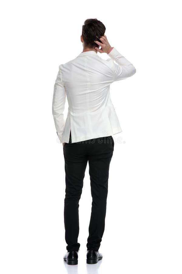 Vue arrière d'un homme confus d'affaires rayant sa tête photographie stock libre de droits