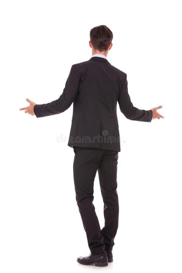 Vue arrière d'un homme d'affaires te souhaitant la bienvenue images stock