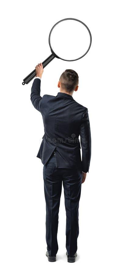 Vue arrière d'un homme d'affaires tenant la grande loupe dans son bras tendu d'isolement sur le fond blanc image stock