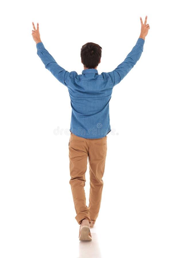 Vue arrière d'un homme occasionnel célébrant la victoire et la marche photo libre de droits