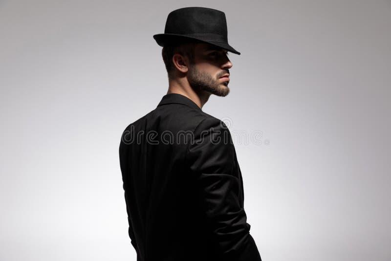 Vue arrière d'un homme occasionnel intéressé fronçant les sourcils image stock