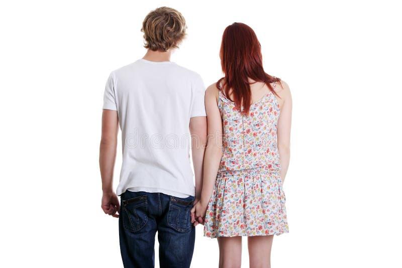 Vue arrière d'un jeune couple retenant leurs mains. photos stock