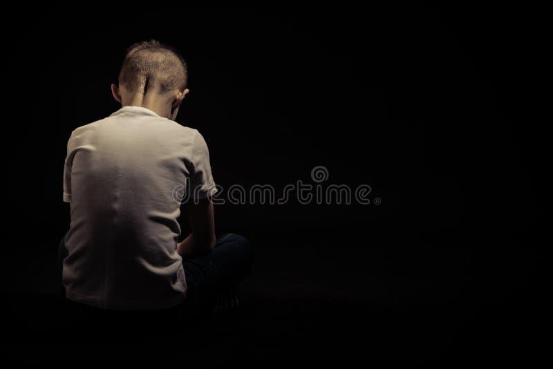 Vue arrière d'un jeune garçon triste assis contre le noir photographie stock