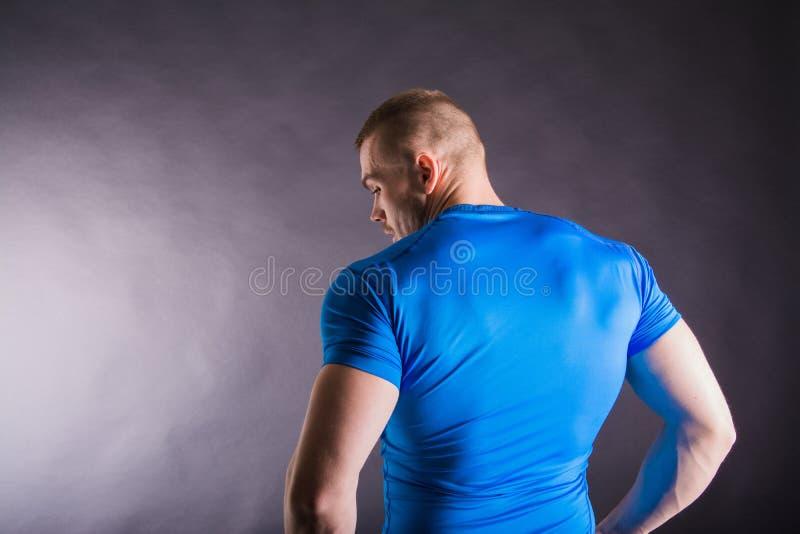 Vue arrière d'un jeune homme musculaire se tenant dans le studio sur le fond foncé images libres de droits