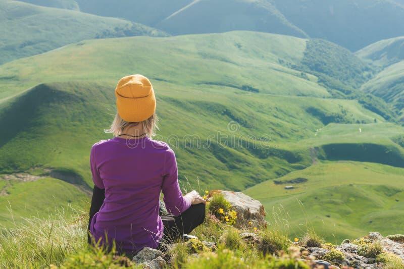 Vue arrière d'un touriste féminin attirant s'asseyant sur les lunettes de soleil de port d'une colline herbeuse Appréciant un jou images stock