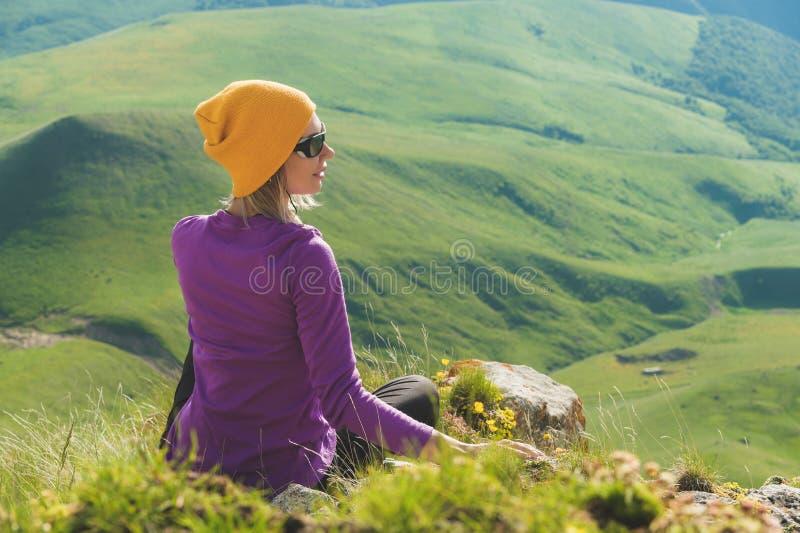 Vue arrière d'un touriste féminin attirant s'asseyant sur les lunettes de soleil de port d'une colline herbeuse Appréciant un jou photos stock