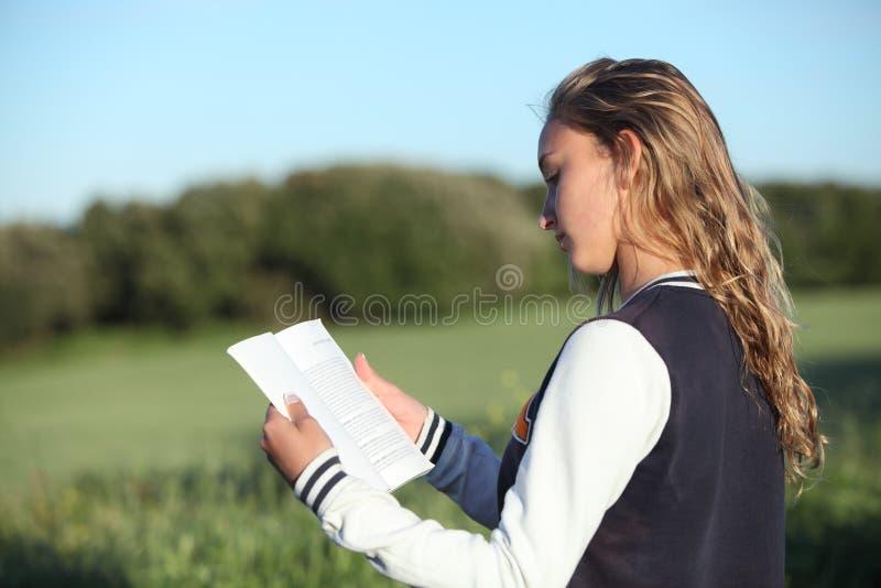 Vue arrière d'une belle fille de l'adolescence lisant un livre photos libres de droits