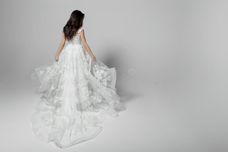 Vue arrière d'une belle jeune femme en épousant la robe blanche de princesse de vol, d'isolement sur un fond blanc Copiez l'espac image stock