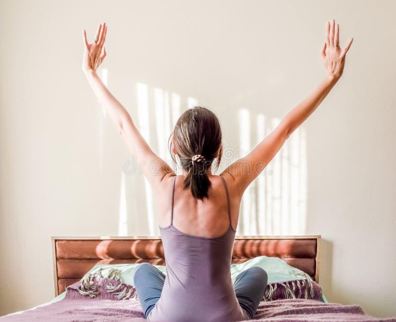 Vue arrière d'une femme caucasienne se réveillant dans le lit et étirant ses bras avec l'espace de copie image stock