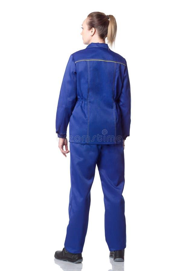 Vue arrière d'une femme dans des vêtements du ` un s de travailleur ou un mécanicien image libre de droits