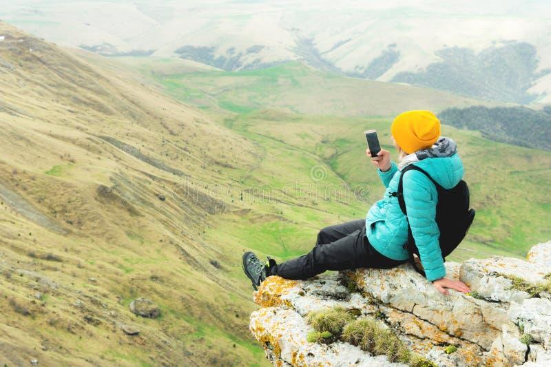 Vue arrière d'une femme s'asseyant sur une roche dans des vêtements d'hiver et utilisant un chapeau sur un smartphone Montagnes d photographie stock