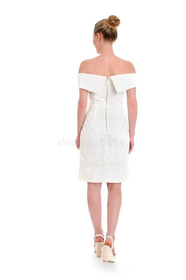 Vue arrière d'une jeune belle femme posant dans un dre court blanc photographie stock libre de droits