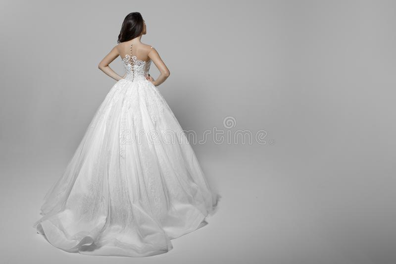 Vue arri?re d'une jeune femme avec de longs cheveux dans la robe l'?pousant blanche, mains sur sa taille, sur un fond blanc photos libres de droits