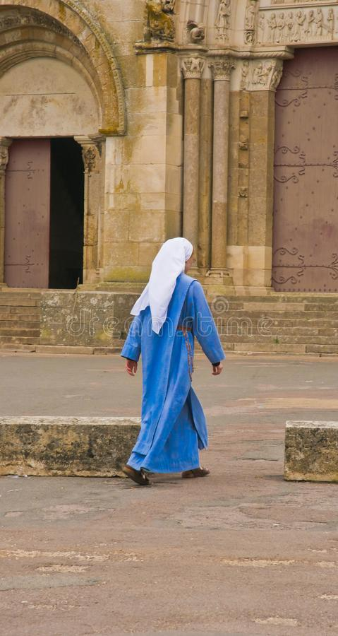 Vue arrière d'une jeune nonne marchant à la porte d'une église photo stock