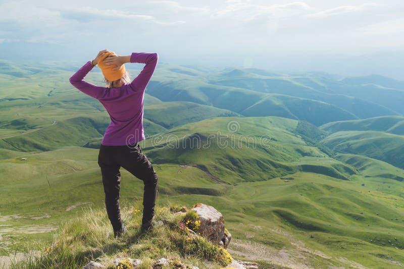 Vue arrière d'une position de touristes femelle attrayante sur les lunettes de soleil de port d'une colline herbeuse Appréciant u photos libres de droits