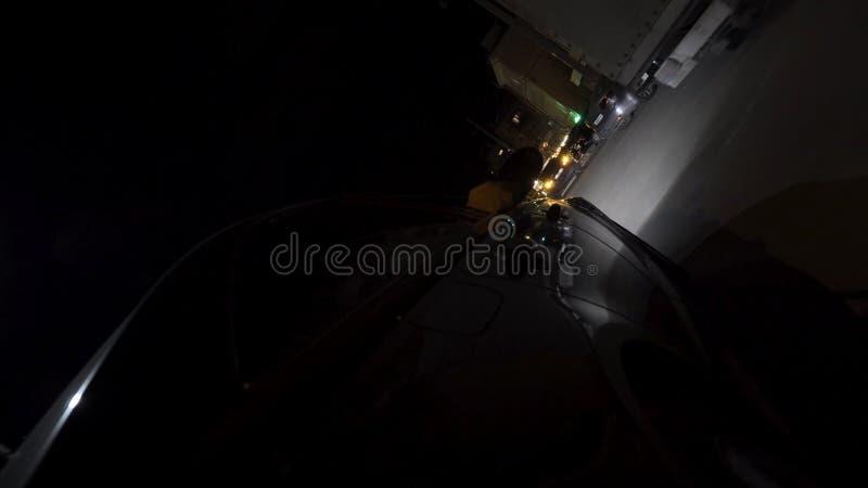 Vue arrière d'une voiture noire se déplaçant par la ville foncée de nuit et commençant à se garer, concept du trafic de nuit long photos stock