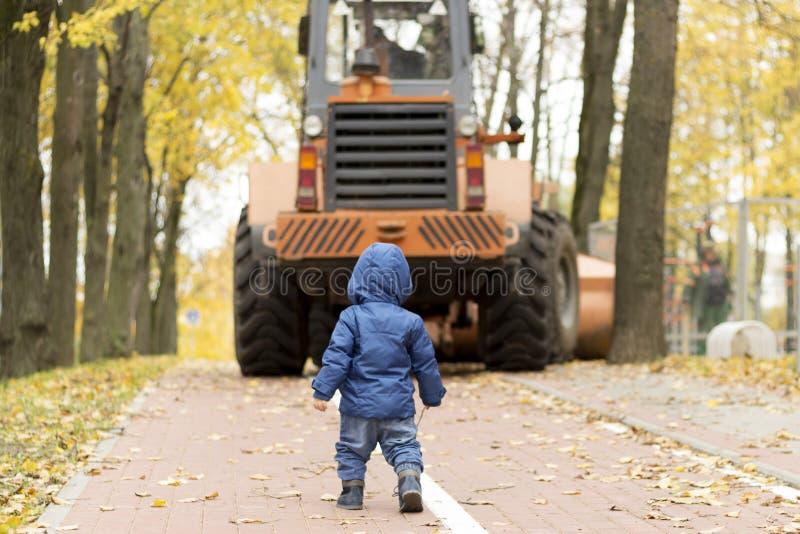 Vue arrière de bébé garçon vis-à-vis de tracteur en parc photo stock