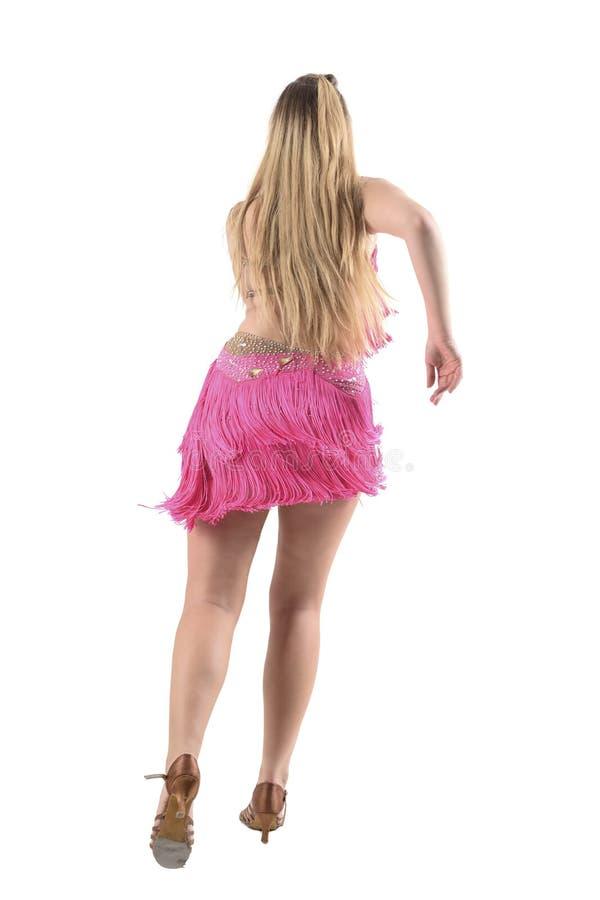 Vue arrière de bachata blond de danse de danseur de jeune latino dans le costume professionnel rose images stock