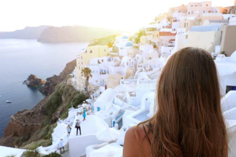 Vue arrière de belle jeune femme dans le village d'Oia, Santorini image libre de droits