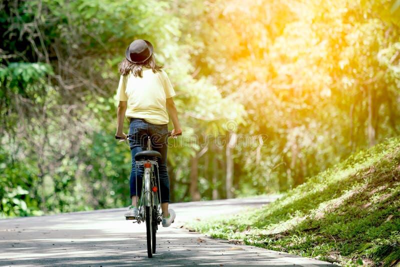 Vue arrière de bicyclette d'équitation de jeune fille dans le jardin photos libres de droits