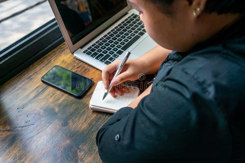 Vue arrière de carnet d'écriture de femme à côté d'ordinateur portable photographie stock