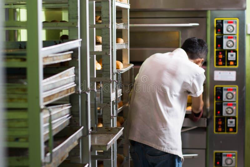 Vue arri?re de chef de p?tisserie faisant le pain cuire au four doux avec le grand four image stock