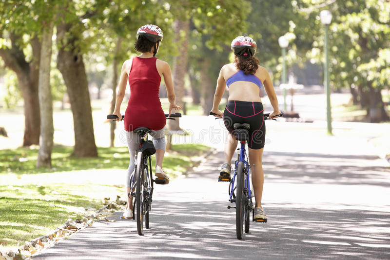 Vue arrière de deux femmes faisant un cycle par le parc images stock