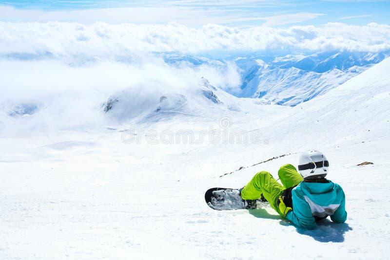 Vue arrière de famale se trouvant sur la neige photographie stock