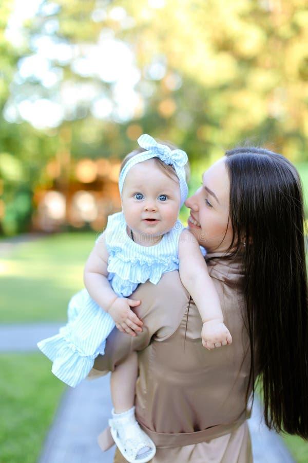 Vue arrière de femme de brune tenant peu de bébé dans le jardin photo libre de droits