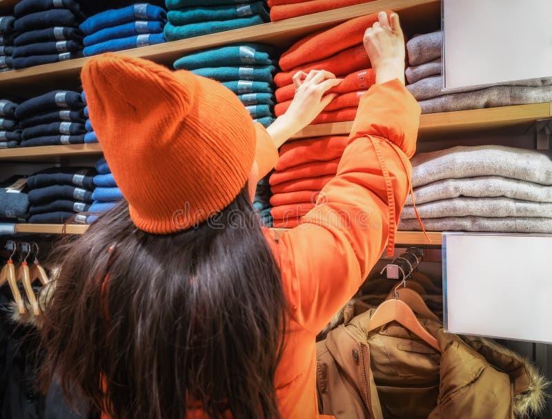 Vue arrière de femme confuse faisant des gestes tout en regardant des vêtements montrés dans le magasin Les chandails de sort de  photo libre de droits