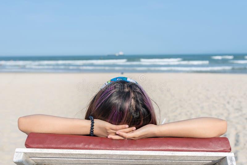 Vue arrière de femme de détente se trouvant sur la chaise de plage d'été image stock