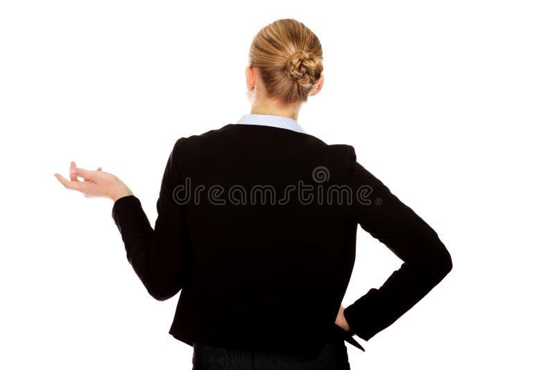 Vue arrière de femme d'affaires gesticulant avec moi ne connais pas le geste photo stock