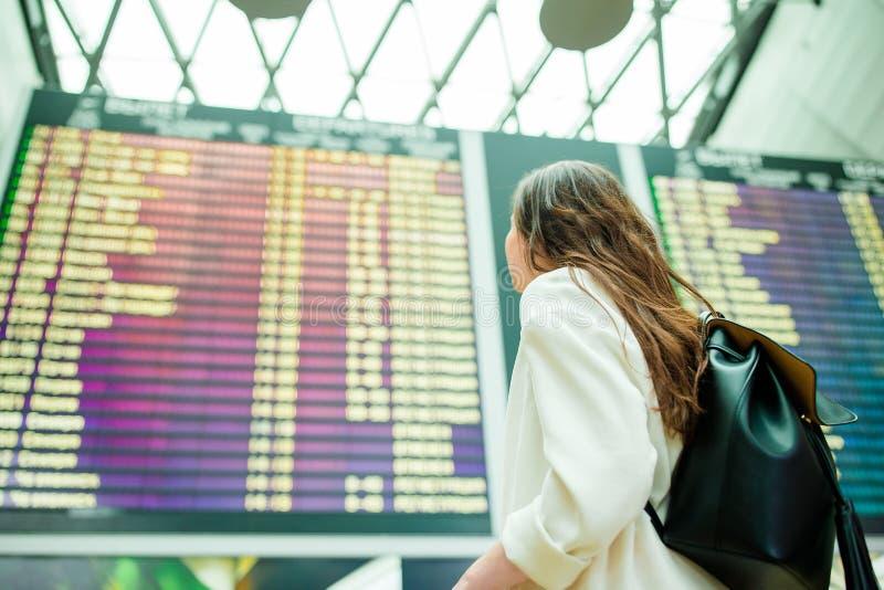 Vue arrière de femme dans l'aéroport international regardant le conseil de l'information de vol vérifiant le vol photographie stock libre de droits