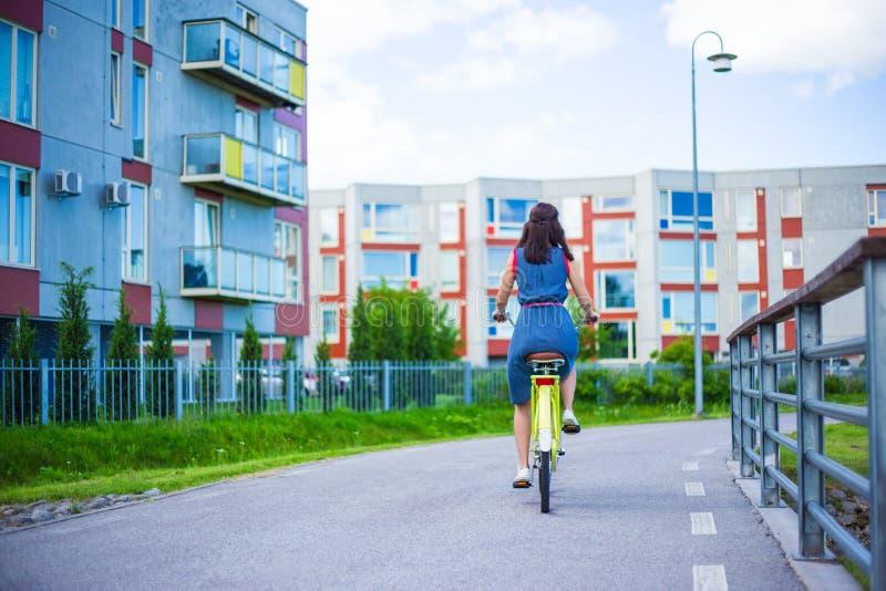 Vue arrière de femme dans la bicyclette de vintage d'équitation de robe dans la petite ville photos stock