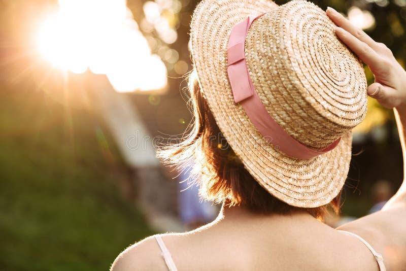 Vue arrière de femme dans la pose de robe et de chapeau de paille photo stock