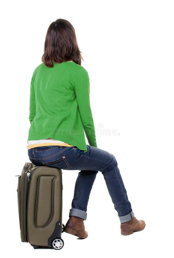 Vue arrière de femme dans le cardigan qui se repose sur une valise photos libres de droits