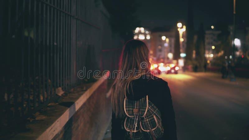 Vue arrière de femme de brune marchant près de la route au temps du trafic La fille passe par la ville tard la nuit seul photo libre de droits