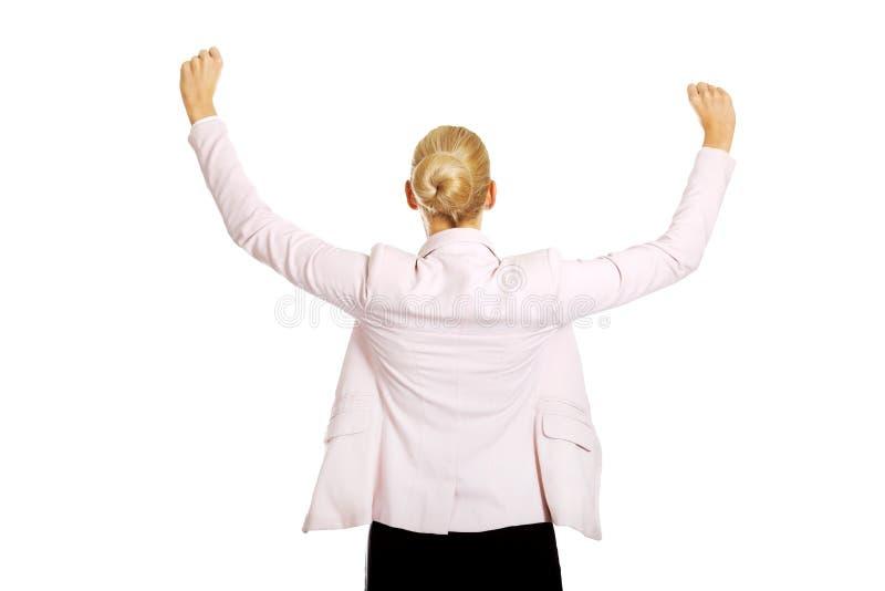 Vue arrière de femme heureuse d'affaires avec des bras  images stock