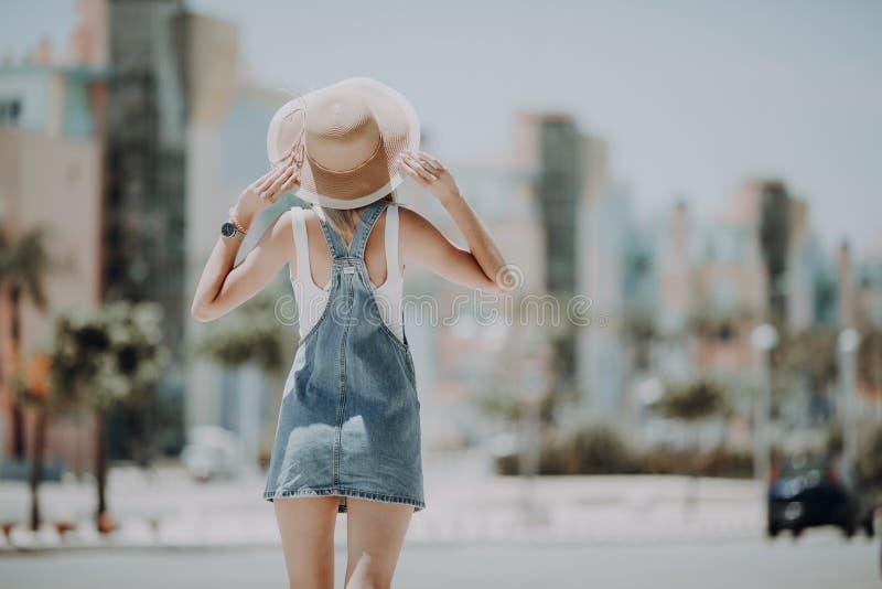Vue arrière de femme marchant sur le chapeau de port de rue de ville appréciant le moment agréable heureux de ses vacances Jour e photos stock