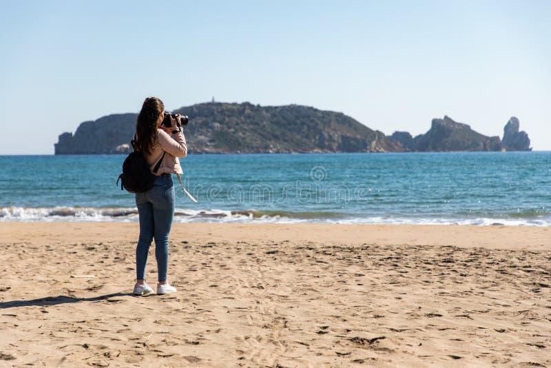 Vue arrière de femme prenant des photos avec la caméra de DSLR des îles de la plage - îles de Medes photographie stock