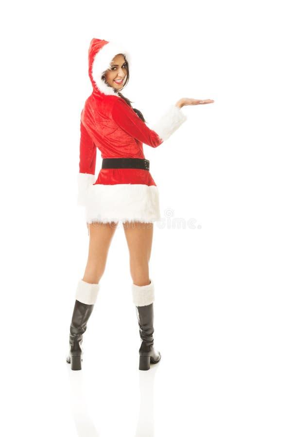Vue arrière de femme de Santa jugeant quelque chose invisible sur la main droite image stock