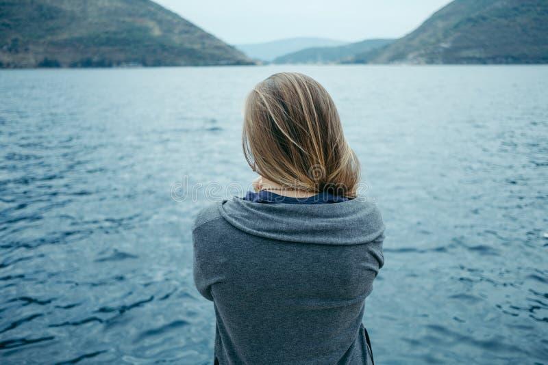 Vue arrière de femme seul pensant et observant la mer avec photographie stock libre de droits