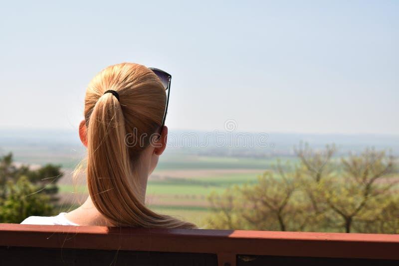 Vue arrière de femme seule regardant pour mettre en place se reposer sur le banc images libres de droits