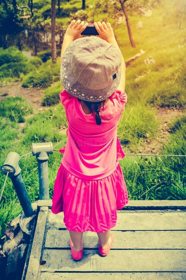 Vue arrière de fille asiatique détendant dehors dans le temps de jour, trave image stock